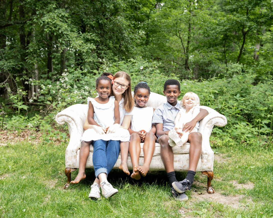 5 adopted children sitting a couch together smiling in Toledo, Ohio
