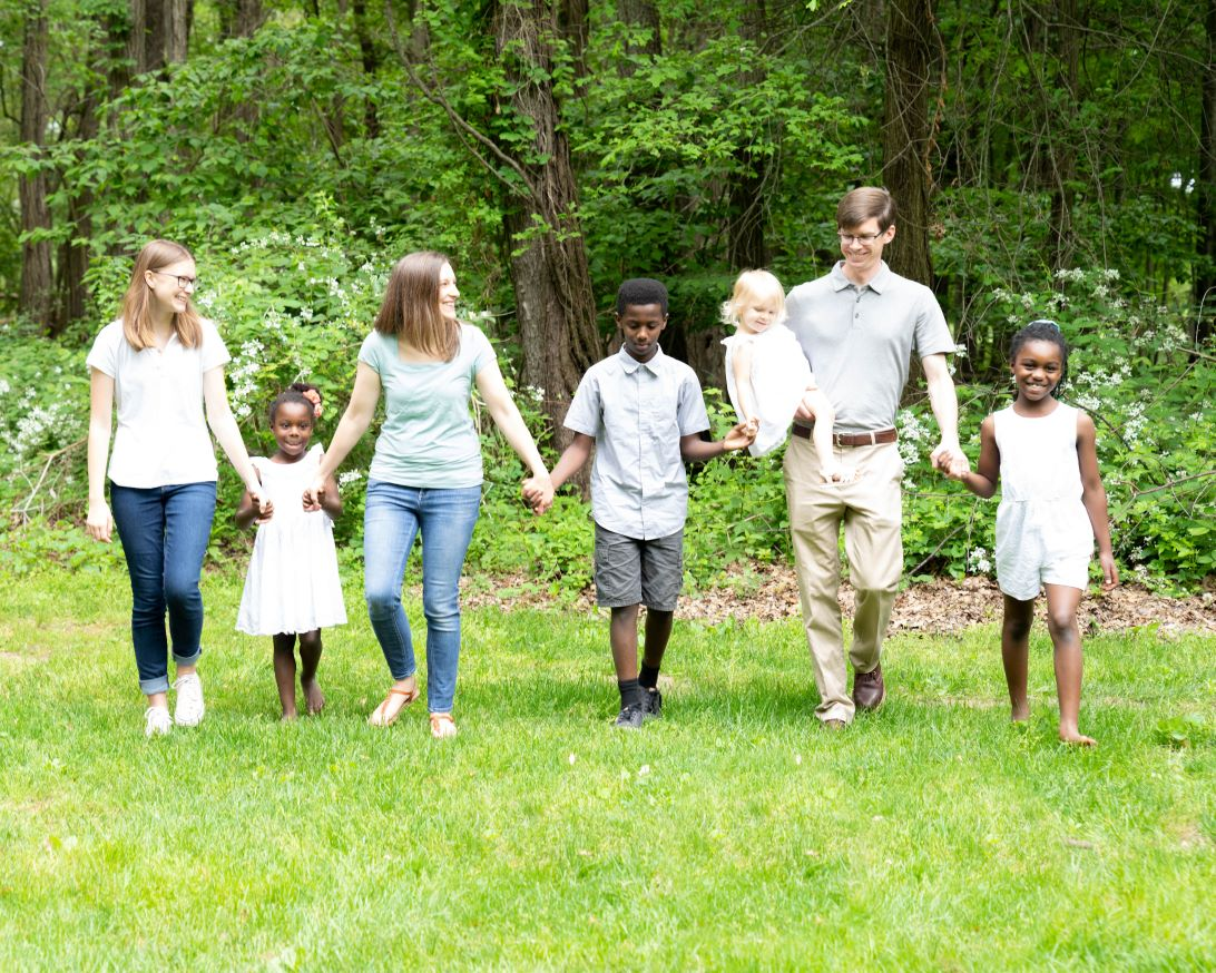 Transracial adopted children holding adoptive parents' hands in a park in Bowling Green, Ohio