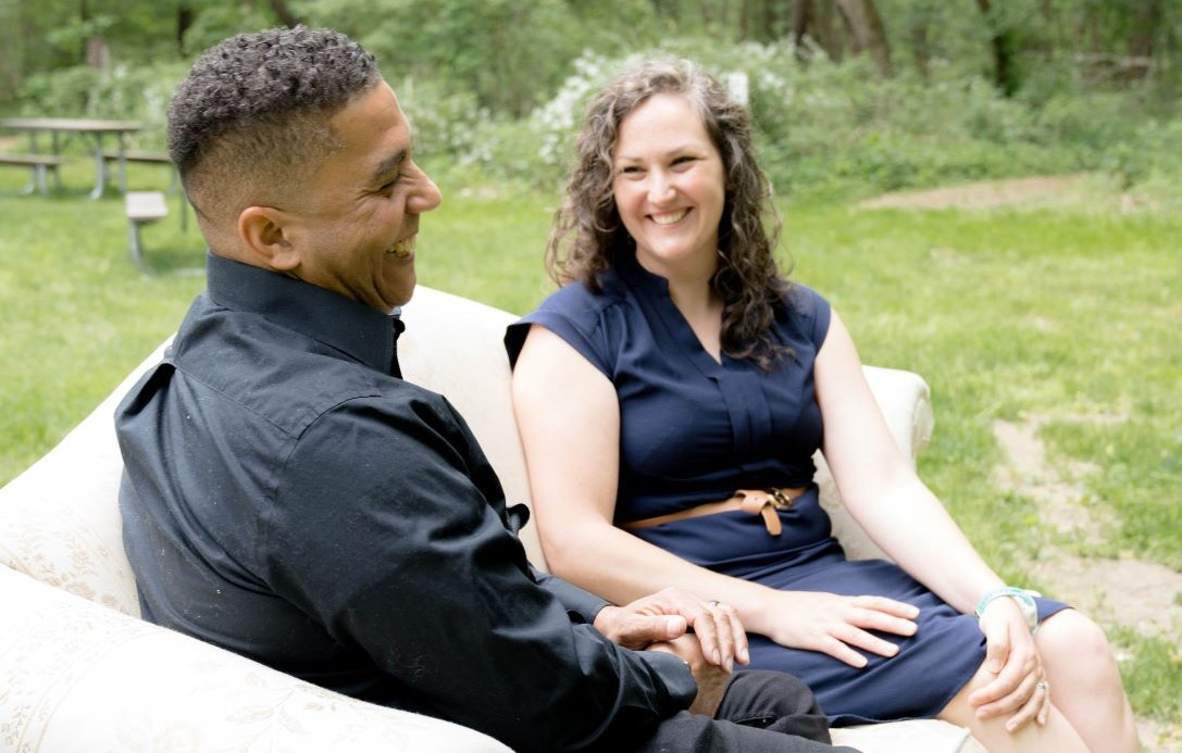 Kevin Hofmann, adult adoptee and Jennifer Mae, birth mom are sitting on a sofa discussing their adoption experiences.