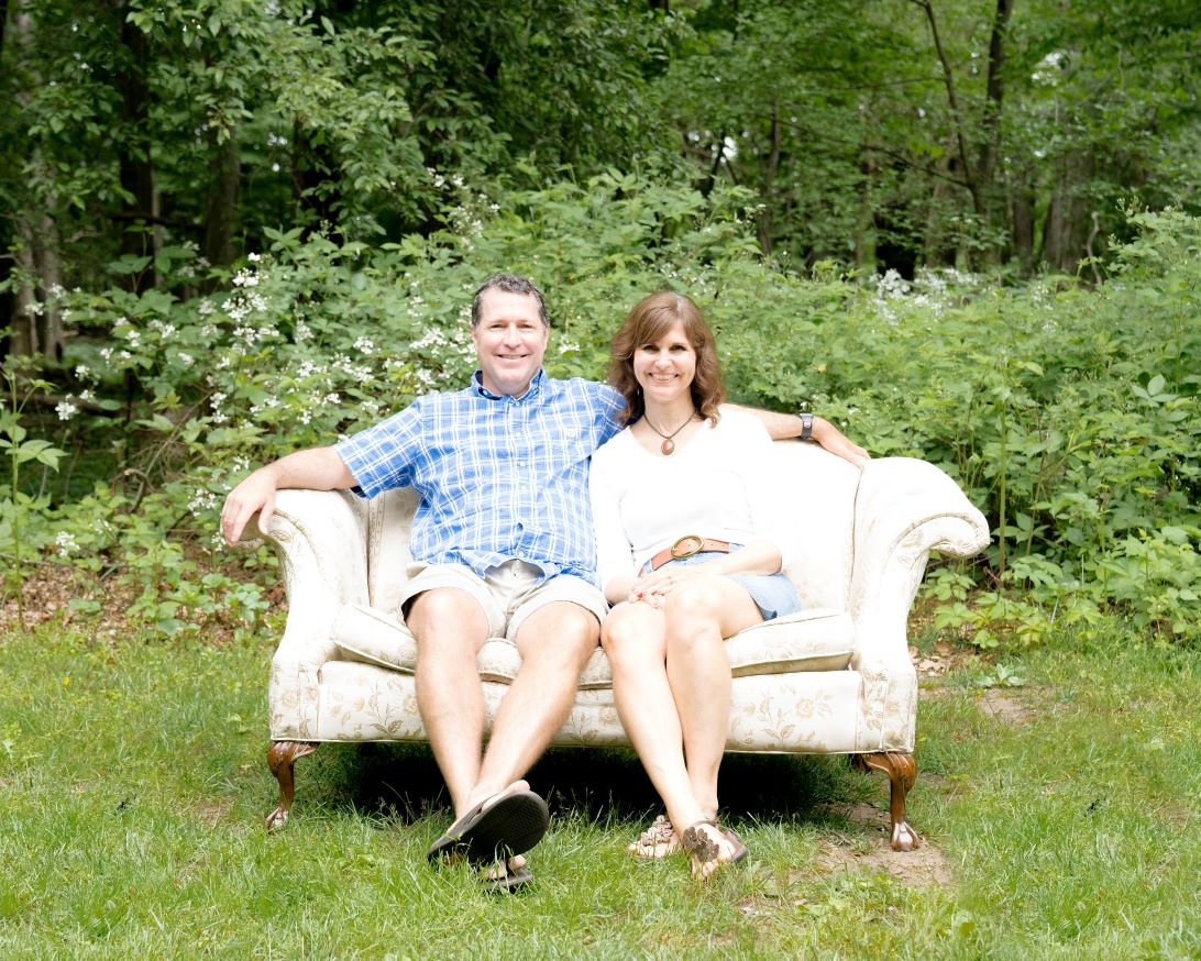 This is Stacy and Jeff smiling and sitting on a sofa. Stacy works for Spirit of Faith Adoptions
