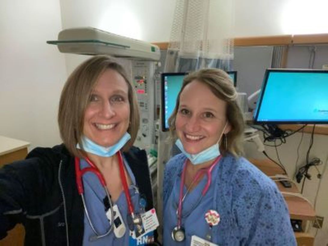 two nurses smiling at the camera in their scrubs at work at in a hospital room