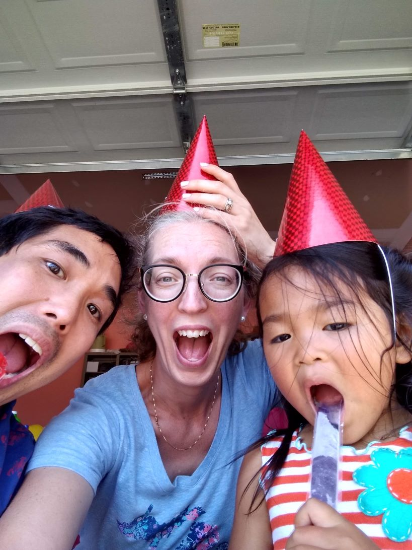 adoptive dad, adoptive mom and adopted young daughter are wearing birthday hats and smiling